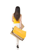 Attractive asian woman holding shopping bags. And posing in studio. Full length portrait. Rear view. Isolated on the white background Royalty Free Stock Photos