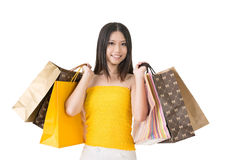 Attractive asian woman holding shopping bags. And posing in studio. Half length portrait. Isolated on the white background Royalty Free Stock Image