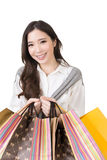 Attractive asian woman holding shopping bags. And posing in studio. Half length portrait. Isolated on the white background Stock Images