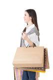 Attractive asian woman holding shopping bags. And posing in studio. Side view and half length portrait. Isolated on the white background Stock Photo
