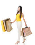 Attractive asian woman holding shopping bags. And walking in studio. Full length portrait. Isolated on the white background Royalty Free Stock Photography