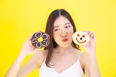 Attractive Asian woman holding two donuts with cute expression over yellow background. royalty free stock image