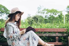 Attractive asian woman reading a book and relaxing at the park.  Stock Photography