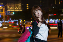 Asian female shopper in city holding shopping bags Royalty Free Stock Photos
