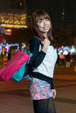 Asian woman shopping in City, looking at camera royalty free stock photography