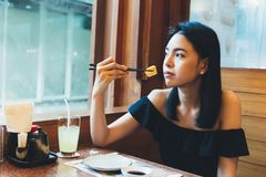 Attractive Asian woman sitting and eating Japanese food alone in the restaurant. royalty free stock photo
