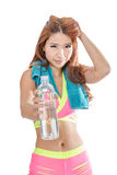 Attractive Asian woman with a towel holding out a water bottle a royalty free stock image