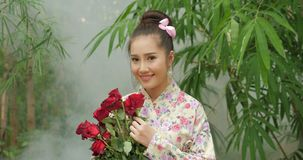 Attractive asian woman in traditional costume with a bouquet of flowers of red roses looking to camera and smiling on stock video
