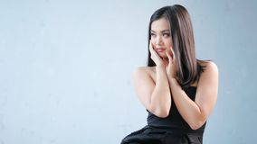 Attractive Asian woman wearing small black dress with naked shoulders posing and enjoying. Having good time at photo studio low angle. Medium shot smiling stock footage