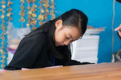 Attractive asian woman writing using pen  behind desk stock images