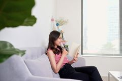 Attractive asian woman writing journal on notebook beside window. In morning time on weekend Royalty Free Stock Photography