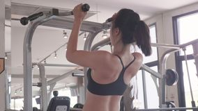 Attractive Asian young muscular girl in sportswear doing pull-ups exercise and chin up at fitness sport gym for strength workout