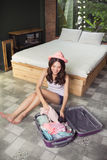 Attractive asian young woman packing a travel bag before going o Royalty Free Stock Photos