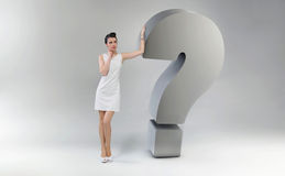 Attractive and astonished woman leaning against the question mar. Attractive and astonished woman leaning against the huge question mark Royalty Free Stock Photography