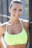 Attractive athlete smiling. A beautiful woman in a sports bra smiling outside Royalty Free Stock Photo