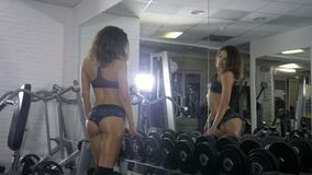 An attractive and athletic girl with dark hair stands near the mirror in the hall and looks at her tight body with hands. On styling with dumbbells turning stock video