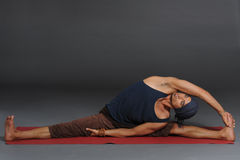 An attractive athletic man doing a yoga pose in studio on grey background. Royalty Free Stock Image