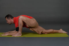 An attractive athletic man doing a yoga pose in studio Royalty Free Stock Image