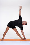 An attractive athletic man doing a yoga pose in studio Stock Photography