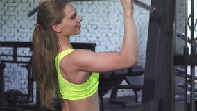 Attractive athletic woman exercising on lat pulldown cable gym machine. Beautiful young fitness woman working out at the gym. Attractive sportswoman exercising royalty free stock images