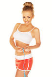 Attractive athletic woman measuring her waist Royalty Free Stock Images