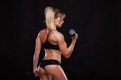 Attractive athletic woman is pumping up muscles with dumbbells, back view isolated on dark background with copyspace Stock Photo