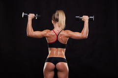 Attractive athletic woman is pumping up muscles with dumbbells, back view isolated on dark background with copyspace Stock Image