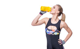 Attractive athletic woman relaxing after workout with shaker isolated over white background. Healthy girl drinks whey protein. royalty free stock image
