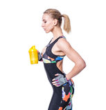 Attractive athletic woman relaxing after workout with shaker isolated over white background. Healthy girl drinks whey protein. stock photo