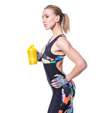 Attractive athletic woman relaxing after workout with shaker isolated over white background. Healthy girl drinks whey protein. Royalty Free Stock Photo