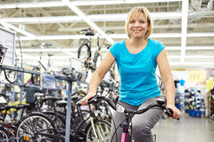 Attractive athletic woman testing bike in store Stock Photos