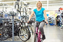 Attractive athletic woman testing bike in store Stock Image