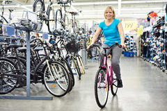 Attractive athletic woman testing bike in store Royalty Free Stock Photo