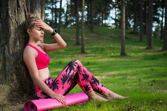Attractive athletic woman wearing smart watch is enjoying last rays of sun for the day after her workout in a forest. Young attractive athletic woman wearing Royalty Free Stock Photo