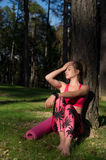 Attractive athletic woman wearing smart watch is enjoying last rays of sun for the day after her workout in a forest. Young attractive athletic woman wearing Royalty Free Stock Images