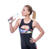 Attractive athletic woman after workout with bottle of water isolated over white background. Healthy girl drinks pure water. Stock Images