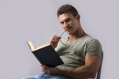 Attractive and athletic young man reading book, looking at camera Royalty Free Stock Images