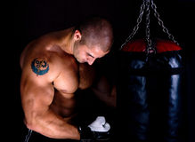 Attractive athletic young man training kickboxing Stock Images