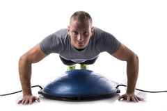 Attractive athletic young man working out with balance board Stock Image