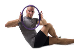 Attractive athletic young man working out with pilates ring Royalty Free Stock Photos