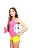 Attractive athletic young woman with a clock and dumbbells Stock Photos