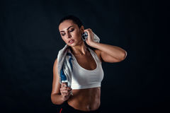 Attractive athletic young woman with perfect body wearing sportswear is posing with a towel against black background. Stock Photography