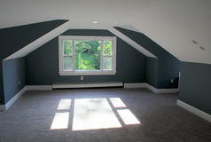 Attractive attic bedroom, with angled ceilings and warm tones of blue paint Stock Photos