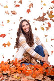 Attractive autumn woman and falling leaves Stock Photos