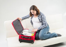 Attractive awaiting woman packing children's clothes into bag Royalty Free Stock Images