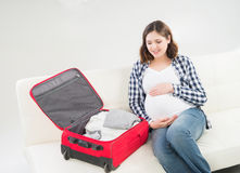 Attractive awaiting woman packing children's clothes Royalty Free Stock Images