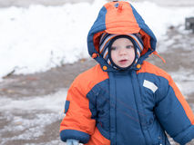 Attractive baby boy playing with the first snow. He smiles and looks snowman. Thick blue-orange jumpsuit bright striped. Attractive baby boy playing with the Stock Photos