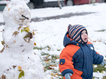 Attractive baby boy playing with the first snow. He smiles and looks snowman. Thick blue-orange jumpsuit bright striped. Attractive baby boy playing with the Stock Images