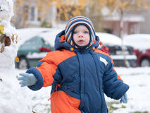 Attractive baby boy playing with the first snow. He smiles and looks snowman. Thick blue-orange jumpsuit bright striped. Attractive baby boy playing with the Stock Photo