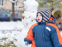 Attractive baby boy playing with the first snow. He smiles and looks snowman. Thick blue-orange jumpsuit bright striped. Attractive baby boy playing with the Royalty Free Stock Images